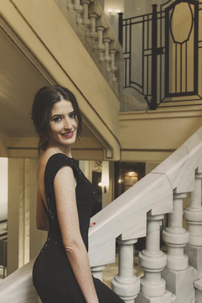 Vestido negro espalda descubierta de Pronovias subiendo escaleras