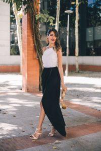 Look invitada boda largo blanco negro escote asimetrico falda abierta pendientes dorados bolso invitada